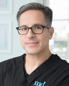 Headshot of Dr. Diaz wearing glasses and black scrubs with MD logo
