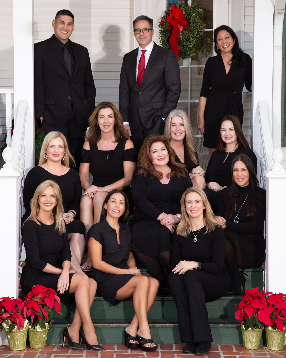 Staff all dressed in black posed on white front steps of the office