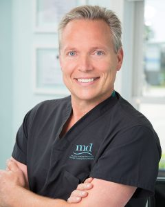 Dr. Christopher Thessen wearing black scrubs with the MD logo